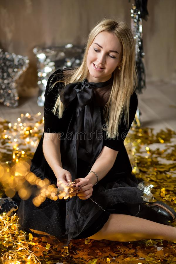 Amazing cute lady celebrating new year birthday party, posing in gold shine background and throwing colorful confetti with silver stock photo