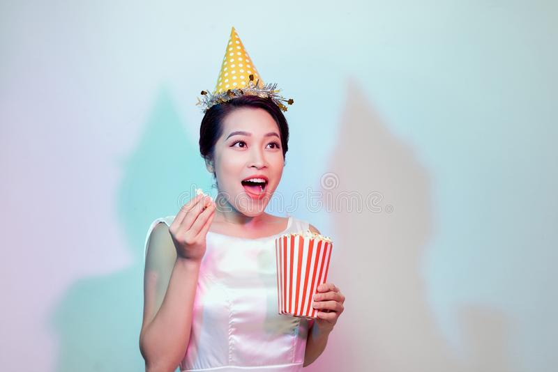 Amazing cute young pretty girl on the light background eats popcorn, wearing a white body dresses, fashionable Pin up girl, cool, stock images