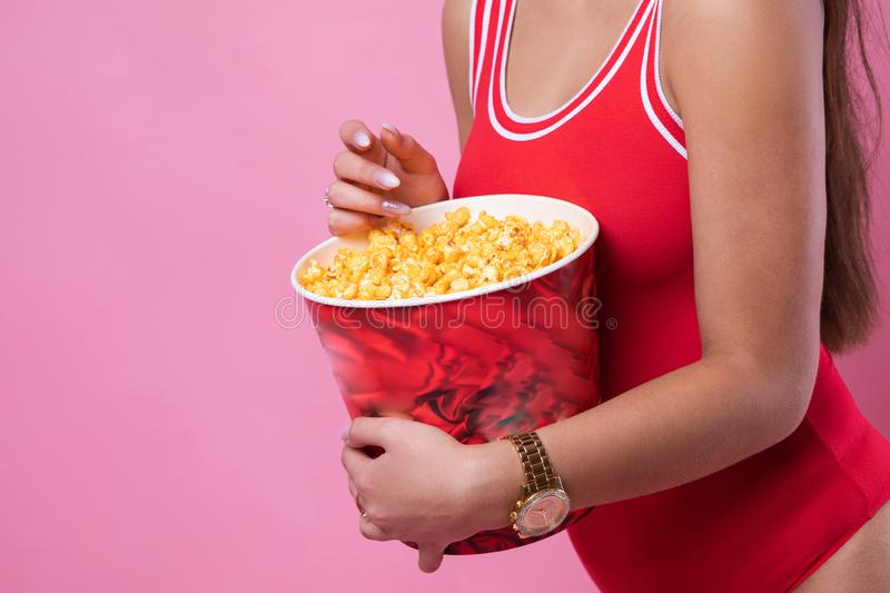 Amazing cute young pretty girl in sunglasses on the pink background eats popcorn and looking at the camera, wearing a red stock image