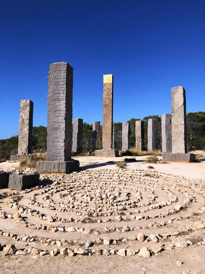 Amazing design - 13 basalt pillars, one of which is covered with gold. Stonehenge in Ibiza. Spain. royalty free stock photo