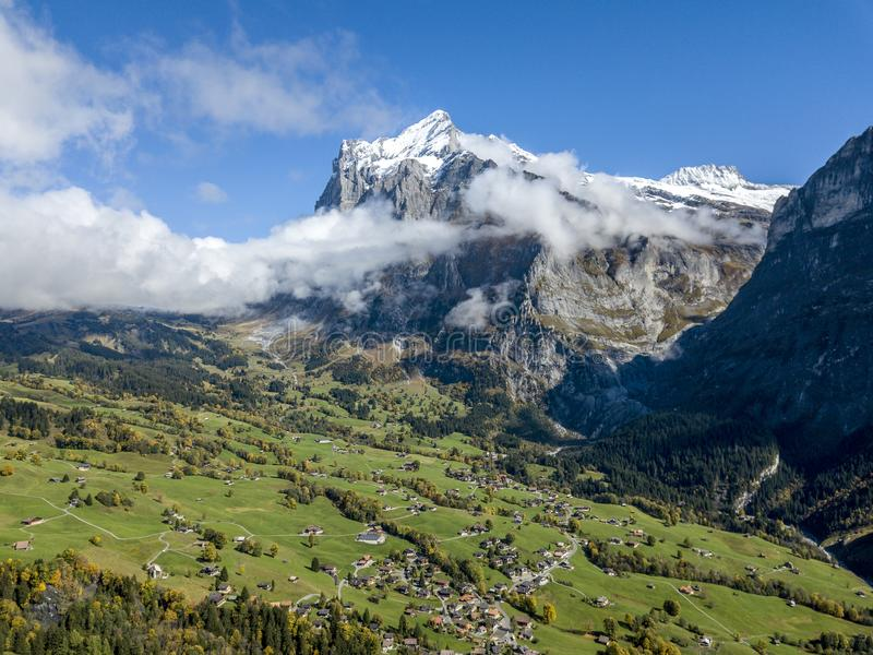 Amazing dream like Swiss alpine mountain landscape. Wooden chalets on green fields and high mountains with snowy peaks background, in Grindelwald of stock images
