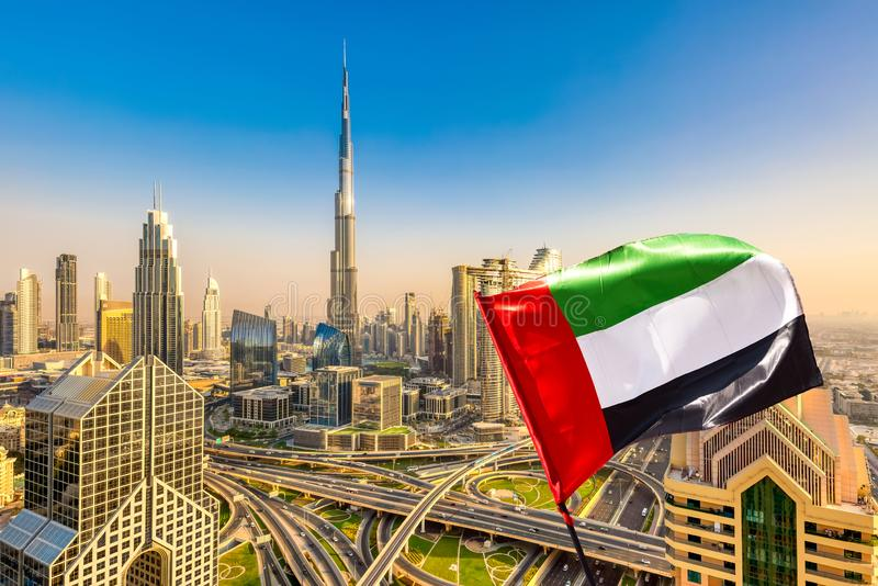 Amazing Dubai skyline cityscape with modern skyscrapers and UAE flag. Downtown of Dubai at sunny day, United Arab Emirates.  stock image