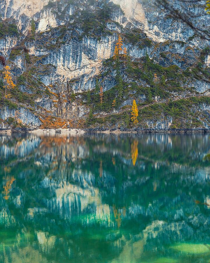 Amazing emerald waters of Lago di Braies in Italy with beautiful reflection. Of the rocky mountains stock photography