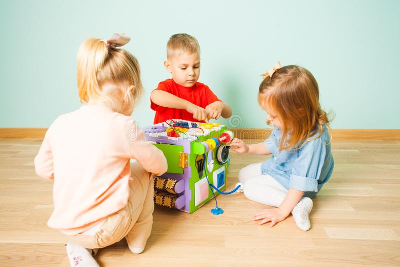 Amazing busy cube and three kids playing with it royalty free stock photography