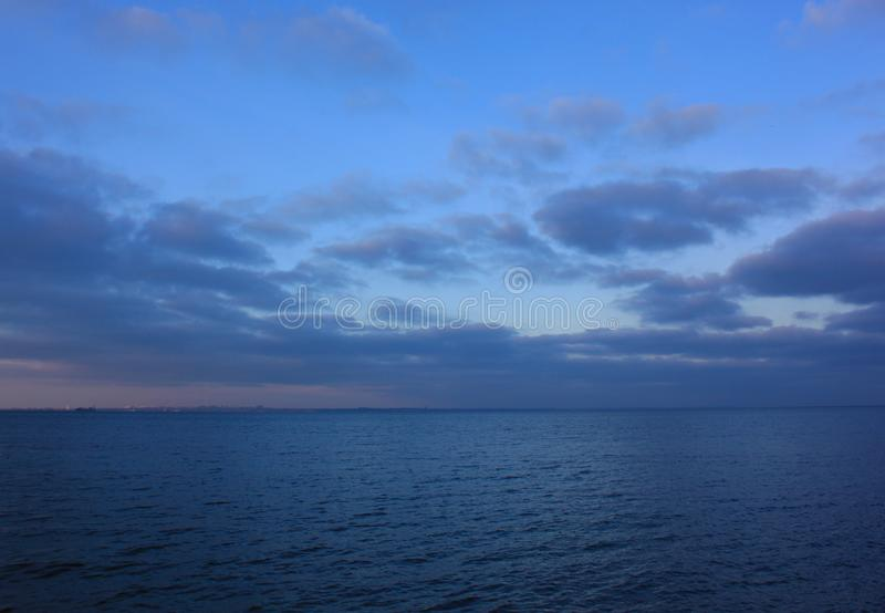Amazing evening landscape of the sea. Ash violet pink blue clouds floating across the sky and dark sea. Beautiful seascape stock photos
