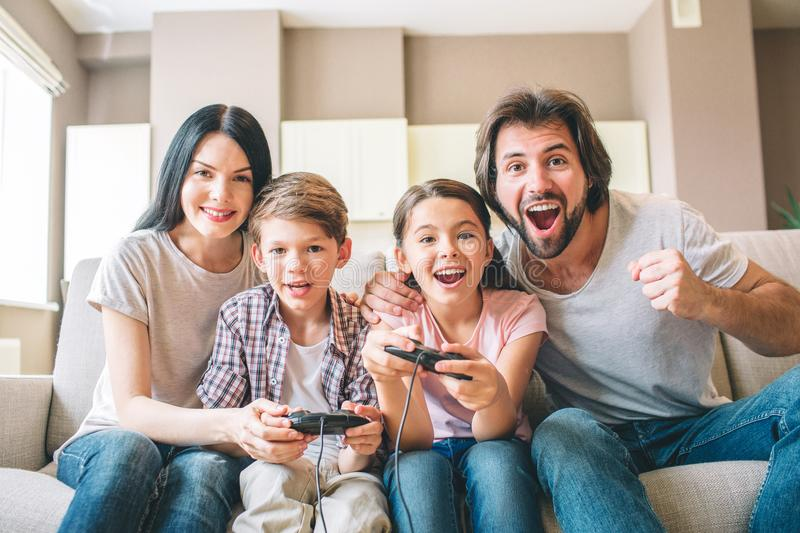 Amazing family sits on sofa. Children are playing on xbox. The game is intense. Guy rejoys. Girl is smiling as well stock photos