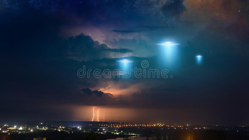 Extraterrestrial aliens spaceship fly above small town, ufo with blue spotlights in dark stormy sky. Amazing fantastic background - extraterrestrial aliens stock photography