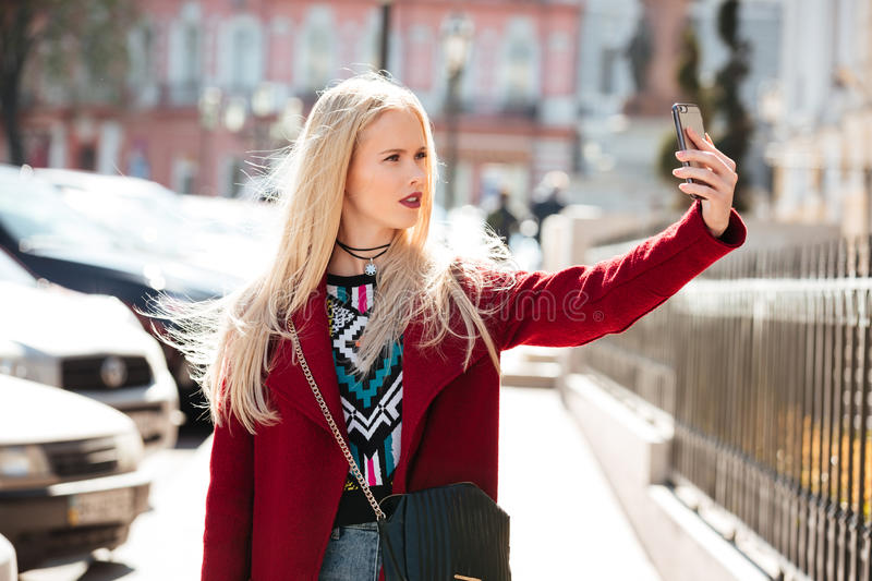 Amazing fashion young blonde woman walking outdoors. Picture of amazing fashion young blonde woman walking outdoors make selfie by mobile phone. Looking aside royalty free stock photo