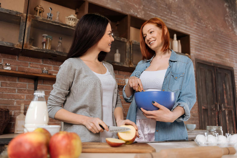 Amazing female smiling to one another. Happy time. Same sex couple wearing casual clothes standing in semi position near the table mixing and cutting apple stock photos