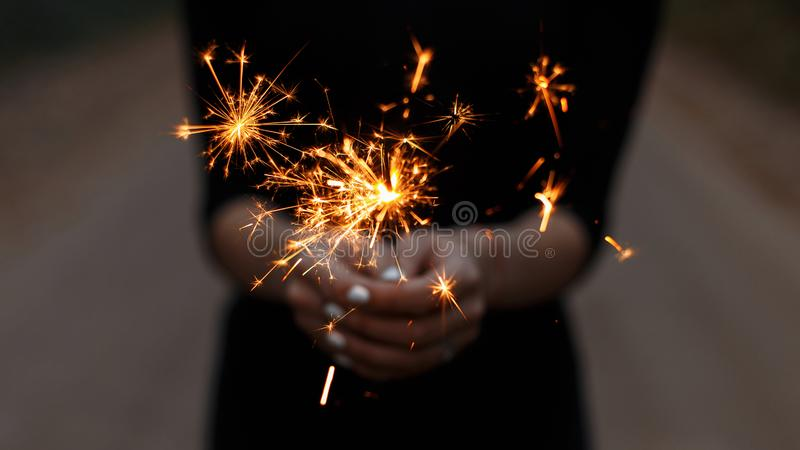 Amazing festive sparklers in the hands of a young woman. Girl celebrates happy birthday. Bright orange sparks with a close up stock photography