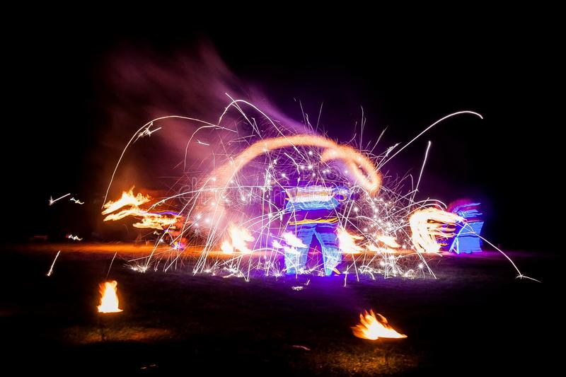 Amazing fire show dance. Fire dancers in beautiful costumes playing with colorful flames.  stock image