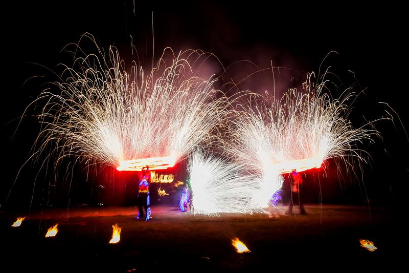 Amazing fire show dance. Fire dancers in beautiful costumes playing with colorful flames.  royalty free stock photos