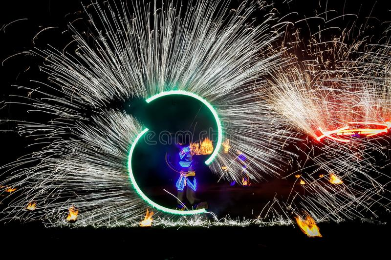 Amazing fire show dance. Fire dancers in beautiful costumes playing with flame.  royalty free stock images