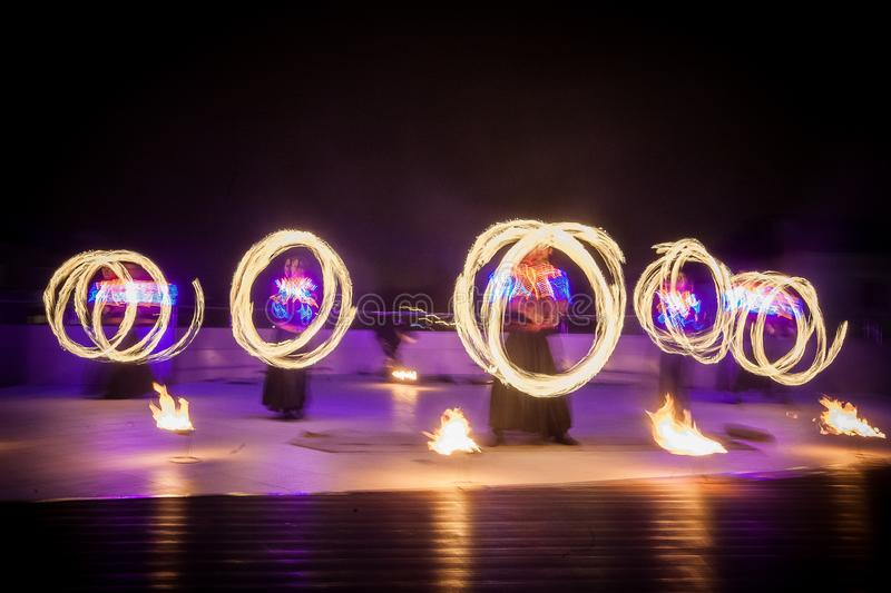 Amazing fire show dance. Fire dancers in beautiful costumes playing with flame. ÑŽ stock photo