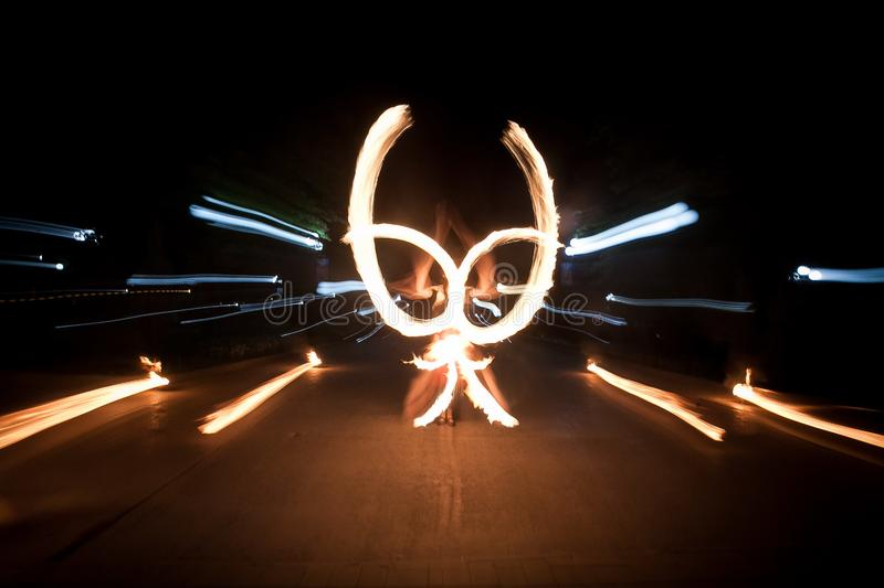 Amazing fire show dance. Fire dancers playing with flame. Butterfly figure royalty free stock images