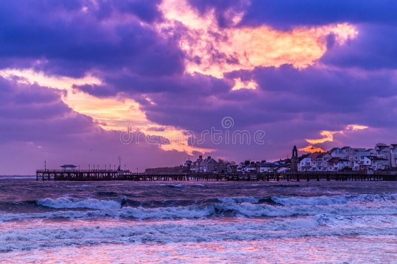 Amazing fire sky at sunrise in seaside town with pier. Amazing pink sky at sunrise in seaside town with pier and waves royalty free stock photo