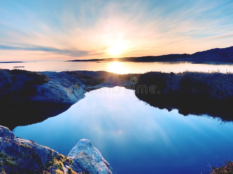 Amazing fire sunrise on the sea bay, rocky shore royalty free stock photography