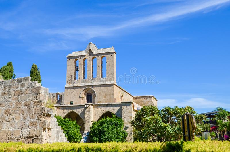 Amazing front side of ancient Bellapais Abbey in Turkish Northern Cyprus captured with the adjacent park and with blue sky. The ruins of the monastery are stock image