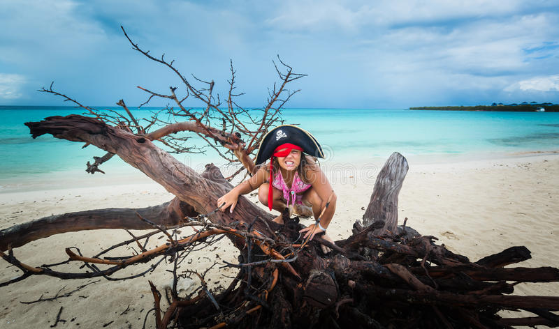 Amazing funny, angry little girl pirate sitting on old dead tree at the beach against dark dramatic sky and ocean background stock photo