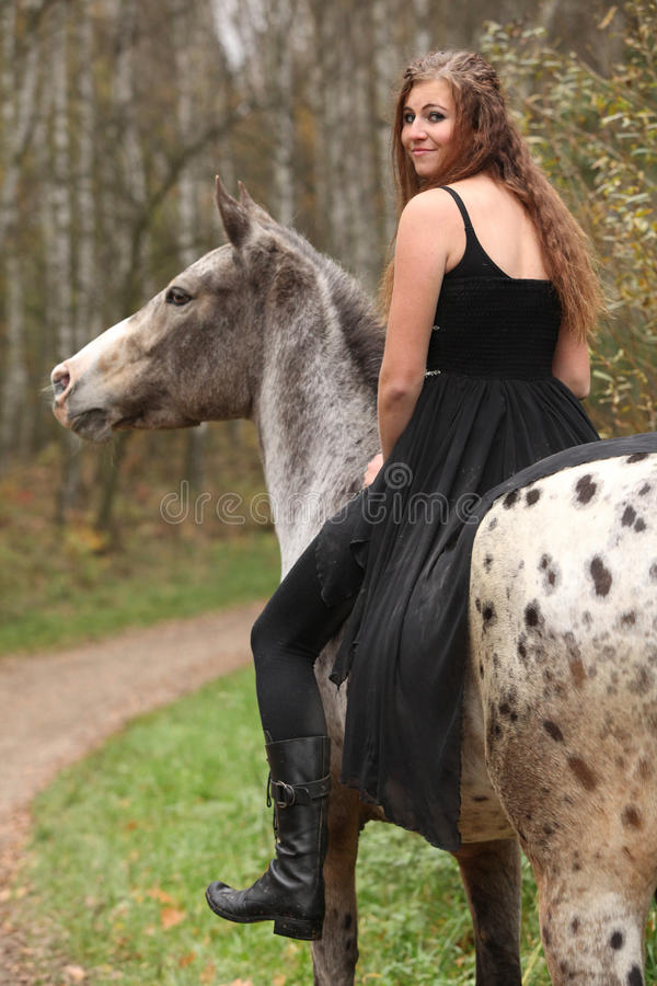 Amazing girl with long hair riding a horse. Without bridle royalty free stock photo