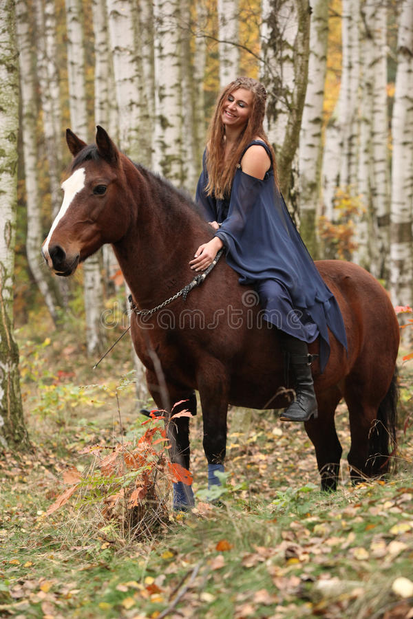 Amazing girl riding a horse without any equipment in autumn fore. Amazing girl riding brown horse without any equipment in autumn forest royalty free stock photos