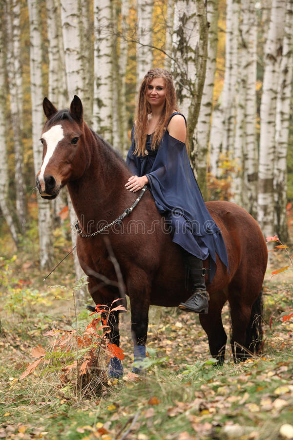 Amazing girl riding a horse without any equipment in autumn fore. Amazing girl riding brown horse without any equipment in autumn forest royalty free stock photo