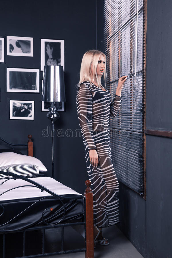 Amazing girl in transparent dress looks out the window with shut stock photography