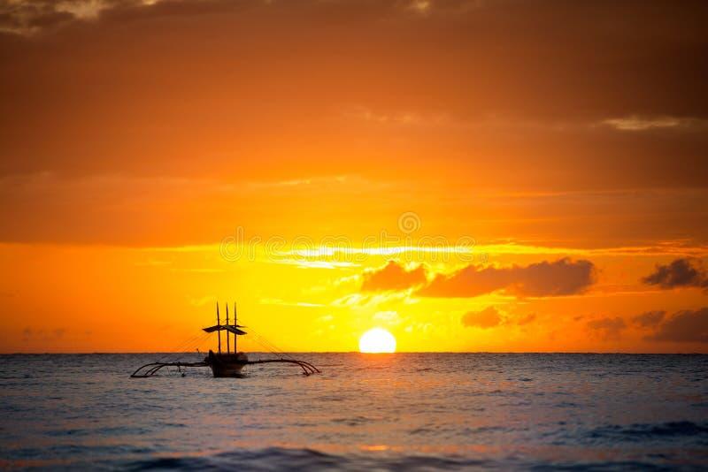 Amazing gold sunset with fishing boat royalty free stock image