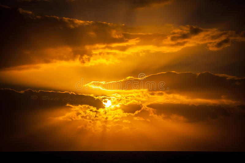Amazing golden sunset. Amazing heavenly golden sunset, sun behind clouds stock images