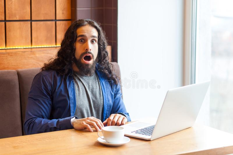 Amazing handsome young adult man freelancer in casual style sitting in cafe with laptop and looking at camera with shocked face, stock photography