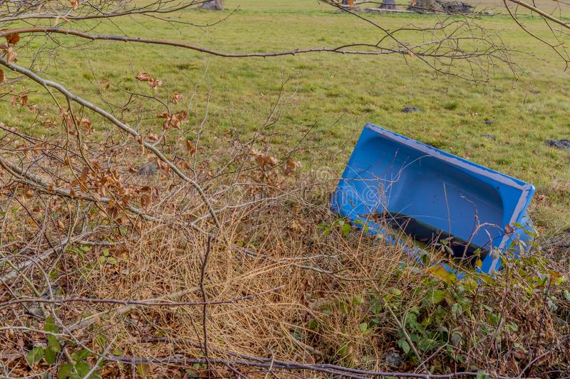 Amazing image of a old blue bathtub lying on a meadow stock photography