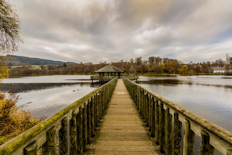 Amazing image of a wooden path leading to a gazebo in the middle of the Doyards Lake. With beautiful reflection in Vielsalm on a wonderful and cloudy autumn day royalty free stock image