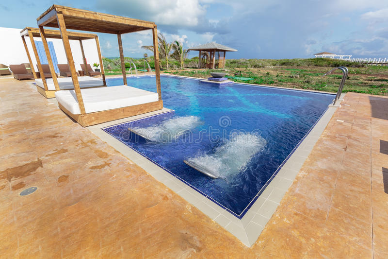 Amazing inviting beautiful view of resort spa and swimming pool with aqua massage beds royalty free stock images