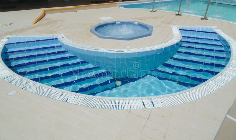 Amazing, inviting gorgeous closeup view of outdoor spa with Jacuzzi and small curved water pool with steps royalty free stock photos