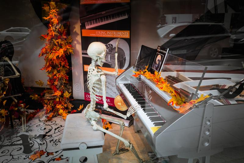 Amazing inviting theatrical view, Halloween decoration with funny skeleton sitting and playing piano at down town Toronto music st royalty free stock images