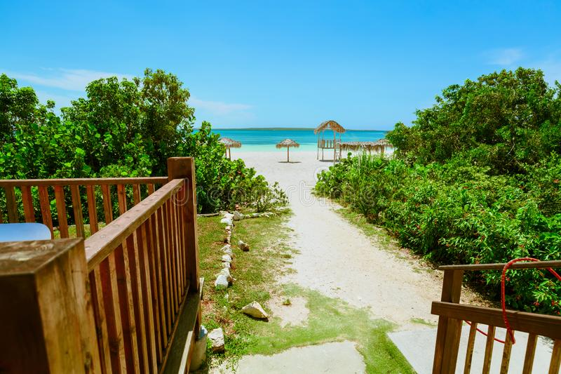 Amazing inviting walk way from a beach bar leading to beautiful white sand beach and ocean at Las Brujas island, Cuba stock photography