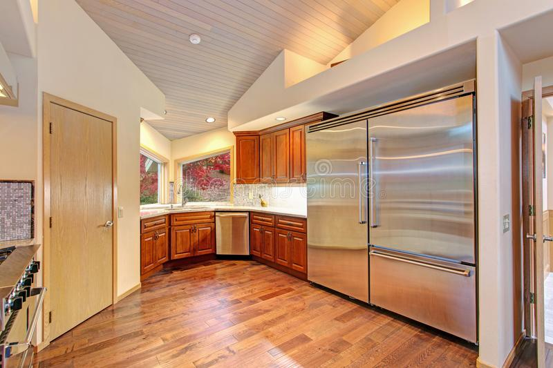 Amazing kitchen with high-end stainless steel appliances. High vaulted ceiling and oak wood floors provide extra warmth in this delightful kitchen royalty free stock images