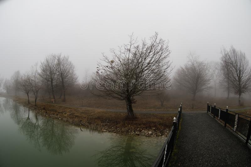 Amazing landscape of bridge reflect on surface water of lake, fog evaporate from pond make romantic scene or Beautiful bridge on l royalty free stock image