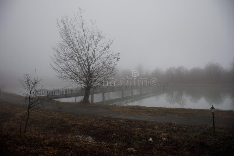 Amazing landscape of bridge reflect on surface water of lake, fog evaporate from pond make romantic scene or Beautiful bridge on l stock image