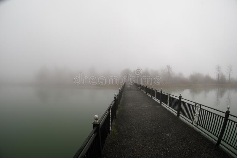 Amazing landscape of bridge reflect on surface water of lake, fog evaporate from pond make romantic scene or Beautiful bridge on l stock photo