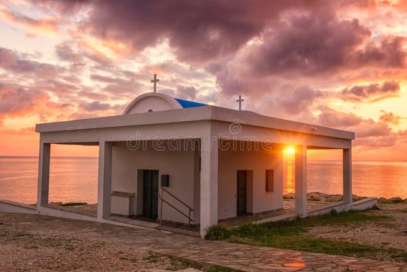 Agioi Anargiroi church at sunrise, Cavo Greco, Cyprus. Amazing landscape of Cyprus Mediterranean seacoast at sunrise with church, colorful clouds and sun. Agioi royalty free stock photos