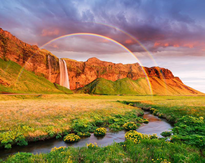 Amazing landscape with a rainbow and a waterfall in Iceland royalty free stock image