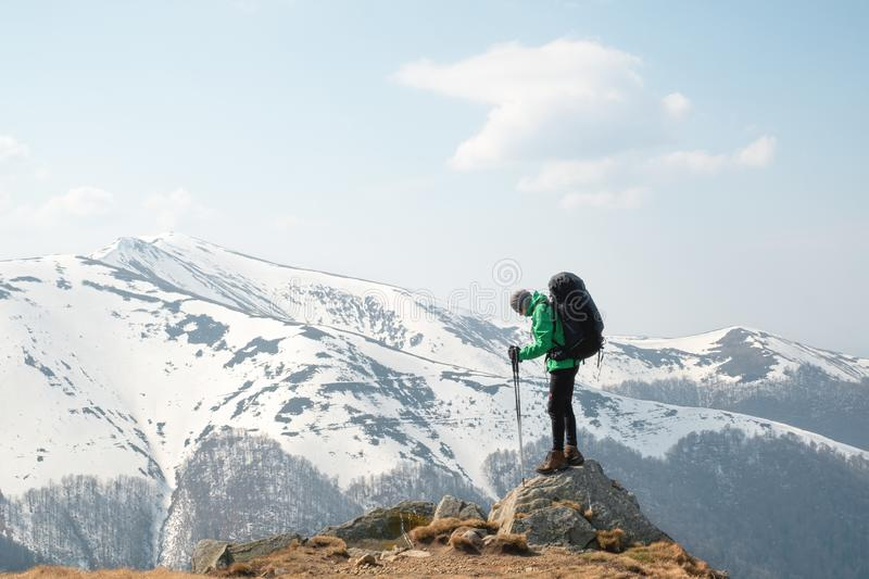 Amazing landscape with snowy mountains range. And hiker with backpack on a foreground stock photography