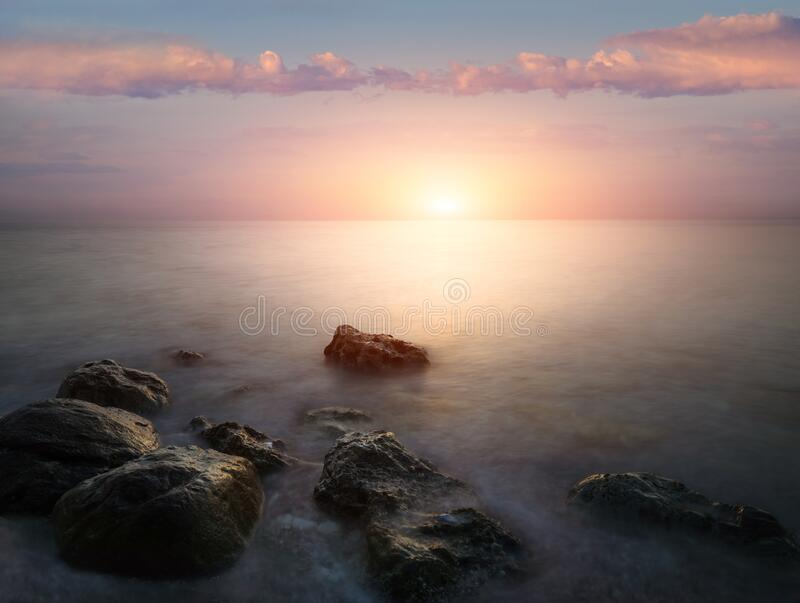 Amazing landscape of sunrise at sea. Colorful morning view of dramatic sky, seascape and rock. Long exposure image. Greece. Medite. Rranean Sea. Concept of stock image