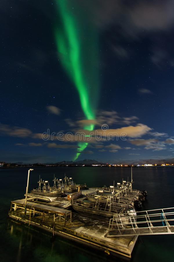 Amazing landscape view with northern lights in background at Lofoten, Norway and fish boat port in front stock photo