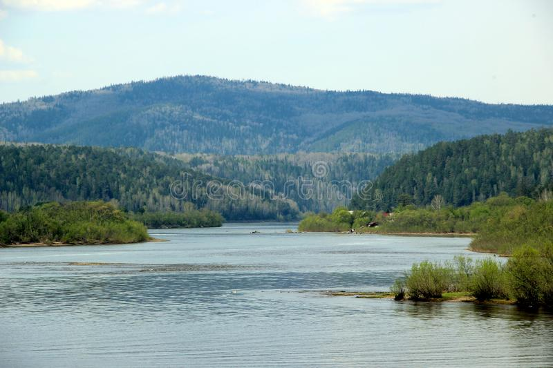 View along the winding river with its shallows towards the wooden mountain stock images