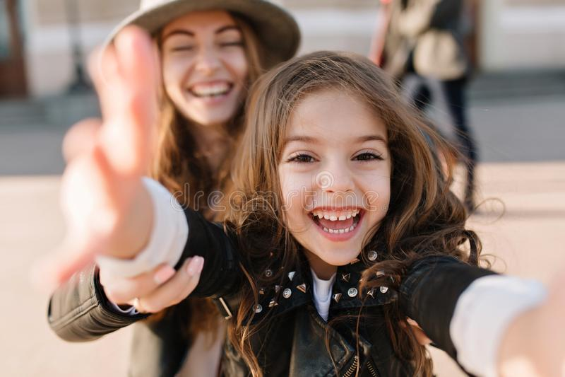 Amazing laughing young woman holding her daughter`s hands, while she having fun in front of camera. Portrait of charming stock photos