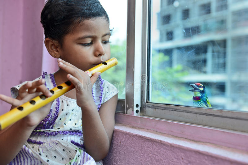 Amazing Listener. A little girl playing flute and a bird looking through the window