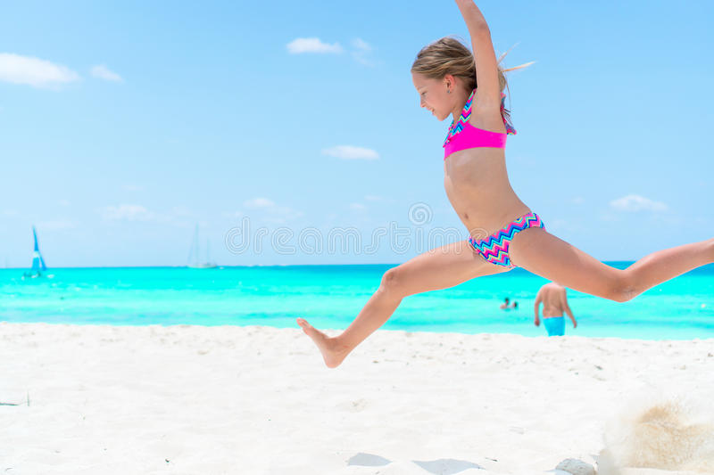 Amazing little girl at beach having a lot of fun on summer vacation. Adorable kid jumping on the seashore royalty free stock photos