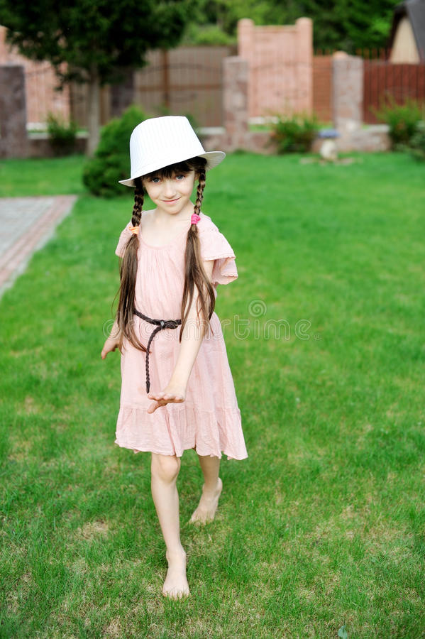 Amazing little girl in pink dress and white hat stock photography